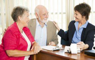 elderly couple sitting talking with advisor